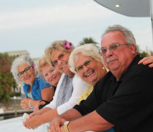 family smiling on upper balcony of yacht