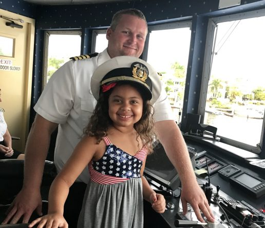 Girl with captain on the bridge of yacht