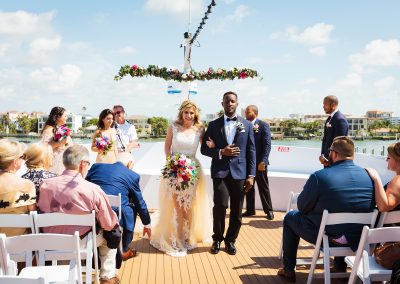 bride and groom leaving wedding ceremony on top deck of yacht
