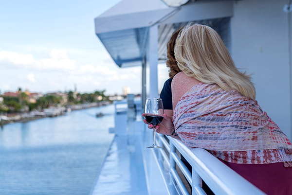 woman holding wine glass looking out from top deck of event cruise
