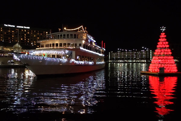 Yacht StarShip I passing by a Christmas tree on the water at night
